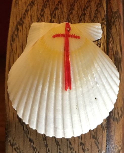 Scallop shell with red cross: be evangelists on your pilgrimage