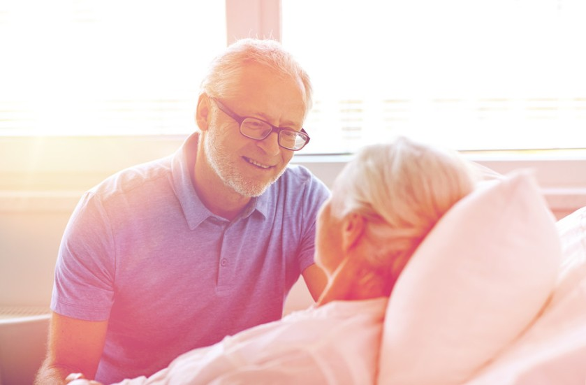 Older woman in hospital with man by her side. Via Shutterstock.