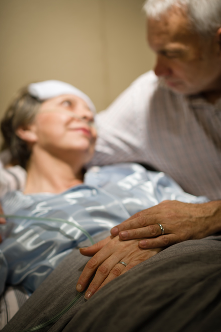 Elderly couple holding hands at a clinic bed