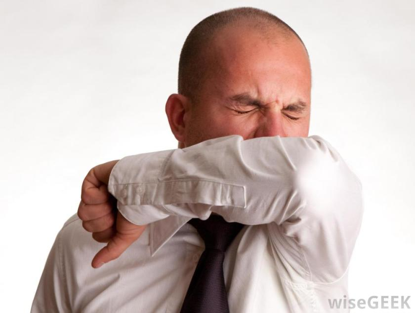 Man sneezing into arm